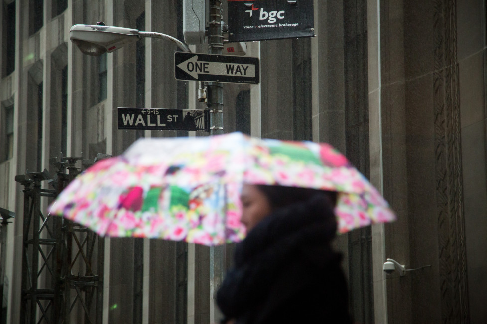 A pedestrian carries an umbrella while walking along Wall Street near the New York Stock Exchange (NYSE) in New York, U.S., on Wednesday, Feb. 24, 2016. U.S. stocks rose, benchmark indexes climbing back from declines of more than 1 percent as crude stabilized near $32 a barrel in New York. Photographer: Michael Nagle/Bloomberg via Getty Images