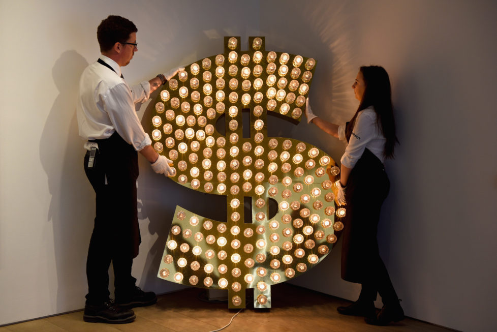 LONDON, ENGLAND - JUNE 08: Two gallery assistants pose with '$, 2001' an installation by Tim Noble and Sue Webster which is going on show at Sotheby's with an estimated value of ?100,000-?150,000 on June 8, 2015 in London, England. The installation forms part of an exhibition of 21 works inspired by the US Dollar which are estimated to have a total value of ?50 million and will go under offer by the auction house on 1st and 2nd July 2015. (Photo by Mary Turner/Getty Images)