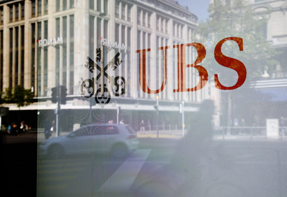 A UBS logo sits in the window of a UBS AG bank branch in Zurich, Switzerland, on Wednesday, April 16, 2014. Swiss and international regulators probably will ask banks to hold more capital in relation to total assets after the U.S. raised leverage-ratio requirements for the biggest lenders, UBS Chairman Axel Weber said. Photographer: Gianluca Colla/Bloomberg via Getty Images