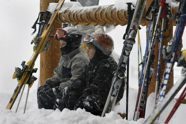 YOUNG KIDS SIT OUTSIDE LODGE DURING HEAVT SNOW AT SITE OF WORLD CUPMENS DOWNHILL.