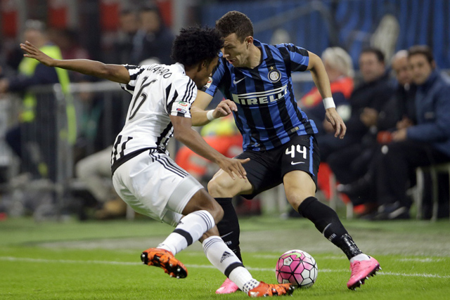 Inter Milan's Ivan Perisic, right, takes on Juventus' Juan Cuadrado during a Serie A soccer match between Inter Milan and Juventus at the San Siro stadium in Milan, Italy, Sunday, Oct. 18, 2015. (AP Photo/Luca Bruno)