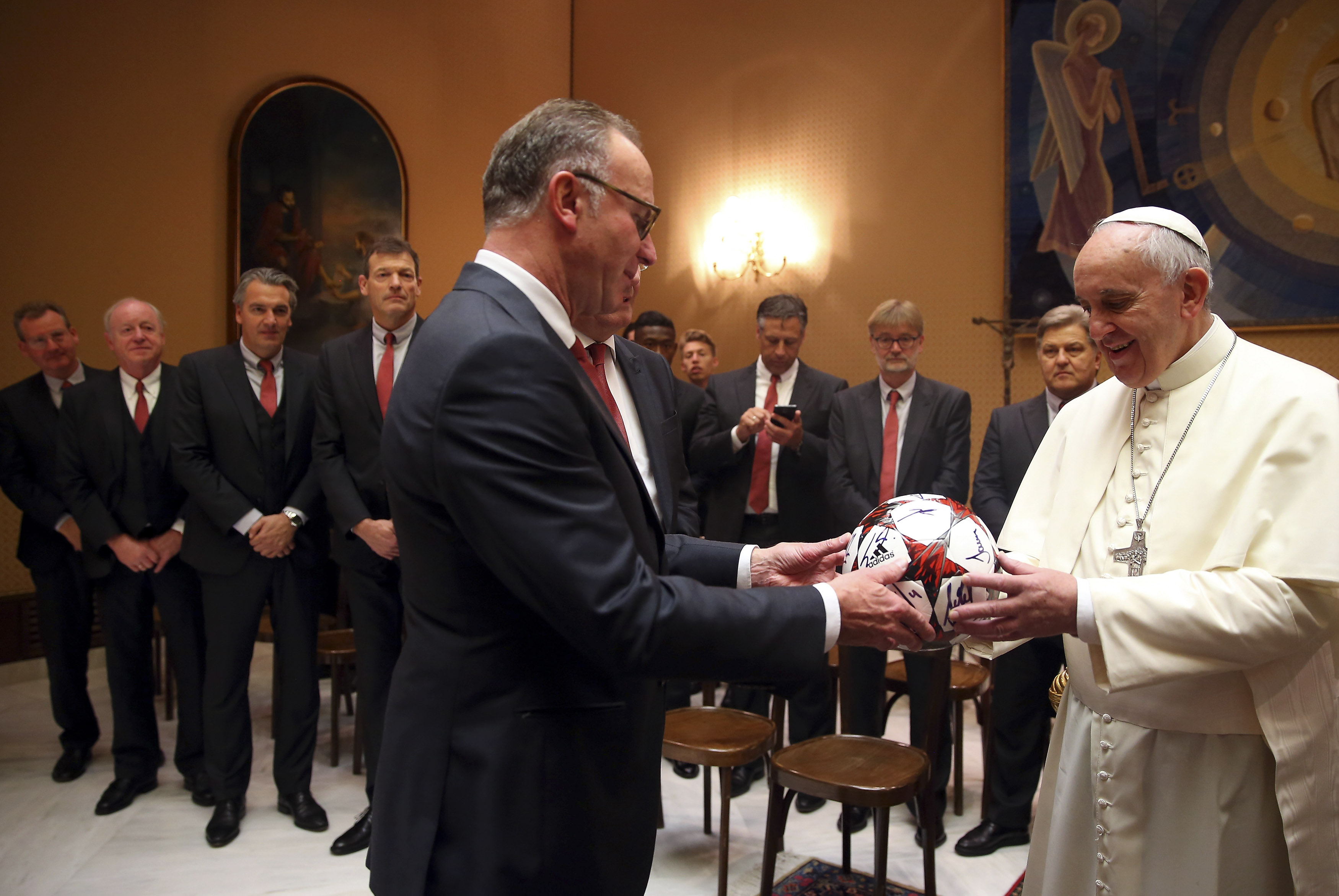 Pope Francis receives an autographed fottball from Bayern Munich's CEO Karlheinz Rummenigge during a private audience with the soccer team at the Palace of the Vatican in Vatican City, October 22, 2014. REUTERS/Alexander Hassenstein/Pool (VATICAN - Tags: SPORT SOCCER RELIGION) - RTR4B4TZ