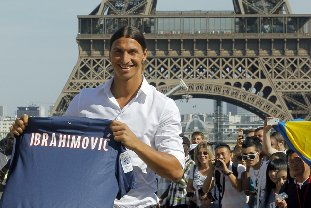 AC Milan striker Zlatan Ibrahimovic, of Sweden, pose in front of the Eiffel Tower with his jersey, in Paris, Wednesday, July 18, 2012 after signing an agreement with the Paris Saint Germain (PSG) club. Ibrahimovic will be the Ligue 1 club's third major signing of the summer, following the arrivals of former AC Milan teammate Thiago Silva and Napoli's Ezequiel Lavezzi. (AP Photo/Jacques Brinon)