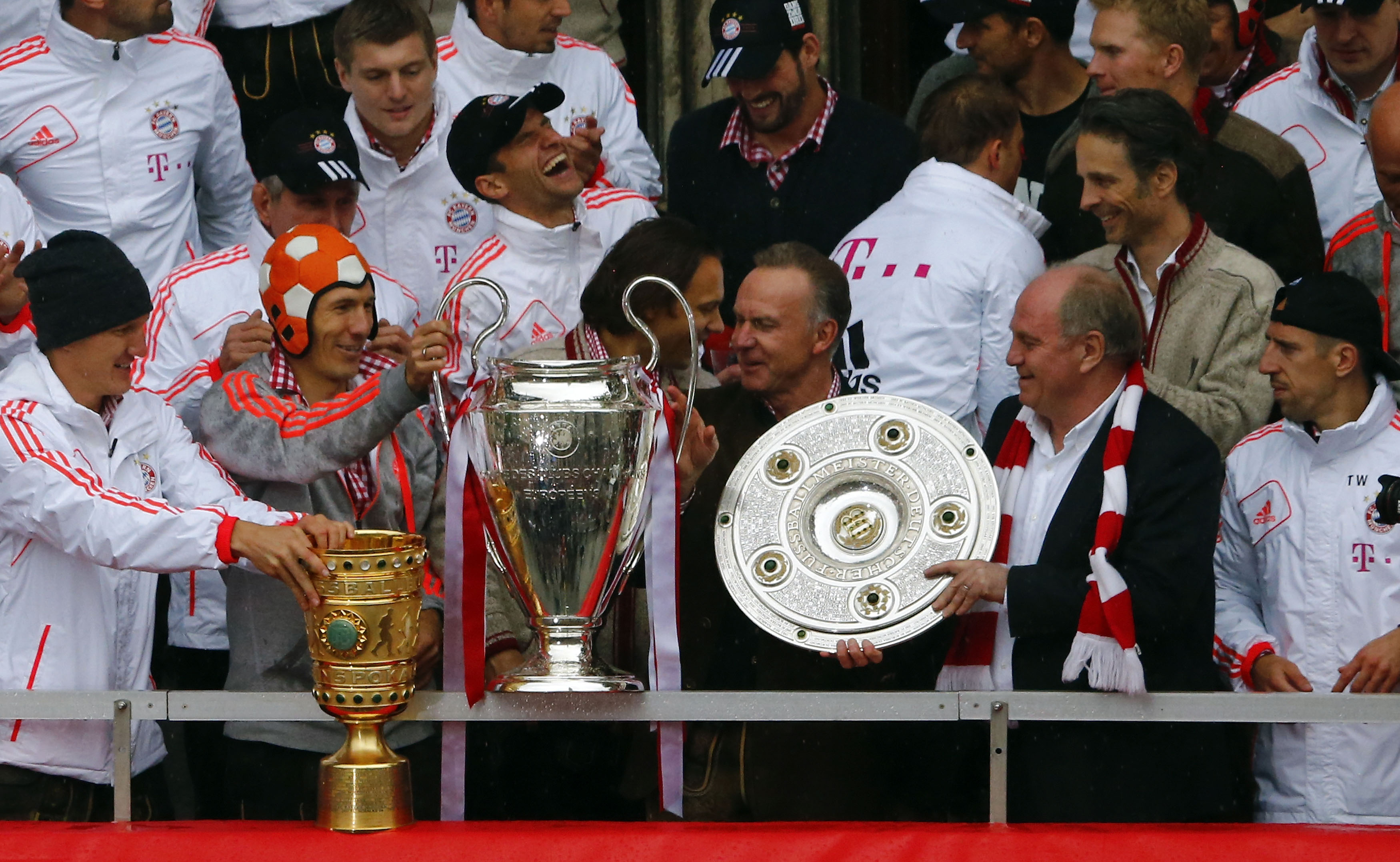 Bayern Munich's players and Chief Executive Karl-Heinz Rummenigge (3R) and President Uli Hoeness (2R) hold up German soccer cup (DFB Pokal), Champions League and German soccer championship Bundesliga trophies as they stand on the balcony of the town hall in Munich June 2, 2013. Bayern Munich completed the treble by beating VfB Stuttgart 3-2 in the German Cup final on June 1, 2013, adding the trophy to the Champions League and Bundesliga titles they have already won this season. REUTERS/Michael Dalder (GERMANY - Tags: SPORT SOCCER) - RTX1099B