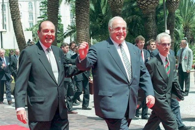 French President Jacques Chirac (L) greets German Chancellor Helmut Kohl at the Palais des Festivals at the opening of the 15 nations European Union Summit in Cannes 26 June. Official at right is unidentified.