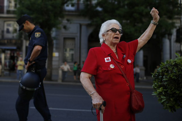 Woman wearing a 15M sticker walks past a police officer as she arrives at Puerta del Sol on third anniversary of 15M movement in central Madrid