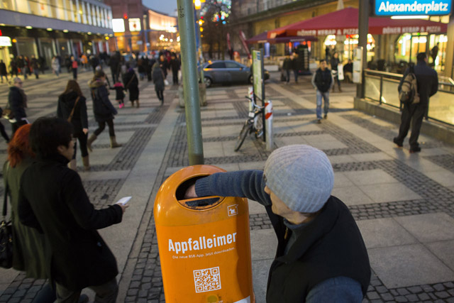 Homeless man searches waste bin for empty bottles at Alexanderplatz square in Berlin