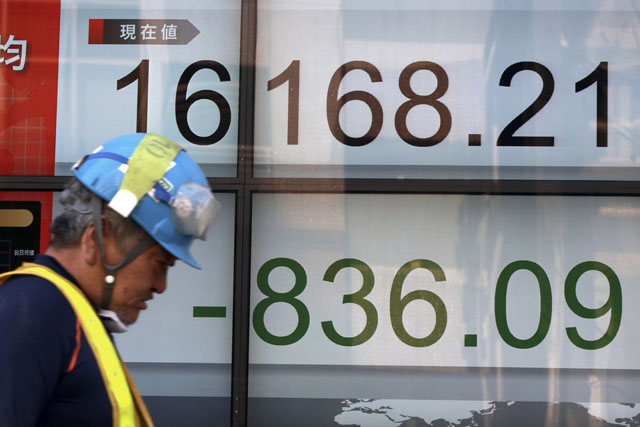 A man walks past an electronic stock board showing Japan's Nikkei 225 at a securities firm in Tokyo, Tuesday, Feb. 9, 2016. Asian markets tumbled Tuesday as renewed jitters about the global economy set off a wave of selling in banking stocks. (AP Photo/Eugene Hoshiko)