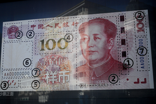 An office building is reflected on a new 100 Yuan note on display outside a bank in Beijing, Monday, Jan. 11, 2016. Barely a week into 2016, Chinese President Xi Jinping is already having a rough time of it, with a plummeting stock market, falling currency, new provocations from boisterous ally North Korea and strong prospects for a victory by the pro-independence opposition in Taiwan, which China sees as a renegade province. (AP Photo/Andy Wong)