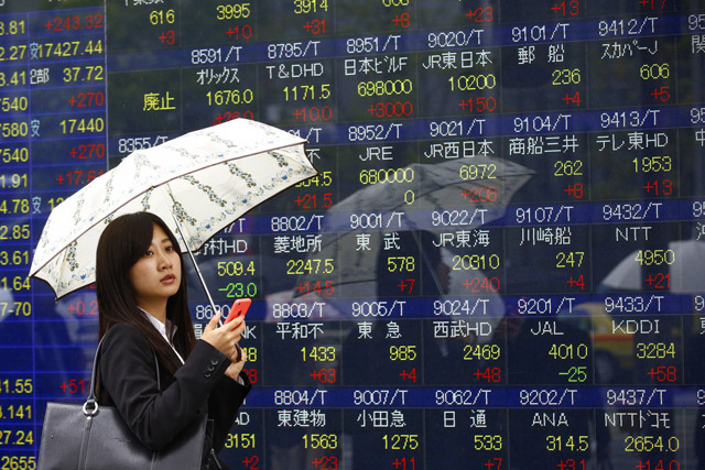 A woman uses a mobile phone in front of an electronic stock indicator of a securities firm in Tokyo, Thursday, April 28, 2016. Japanese stocks rallied Thursday as the latest economic data spurred hopes for more central bank stimulus, leading gains in other Asian benchmarks after the Fed left interest rates unchanged. (AP Photo/Shizuo Kambayashi)