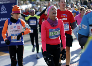 Runner reacts after crossing the finish line of the 2014 New York City Marathon in Central Park in Manhattan
