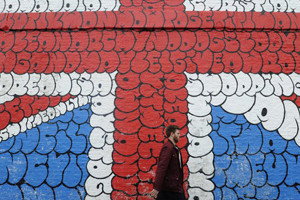 epa03105776 A man walks by a giant graffiti mural depicting the Union Jack in London, Britain, 14  February 2012. Credit ratings agency Moody's has issued official notice to Britain and the Bank of England that their credit ratings are at risk of a potential downgrade.  EPA/FACUNDO ARRIZABALAGA
