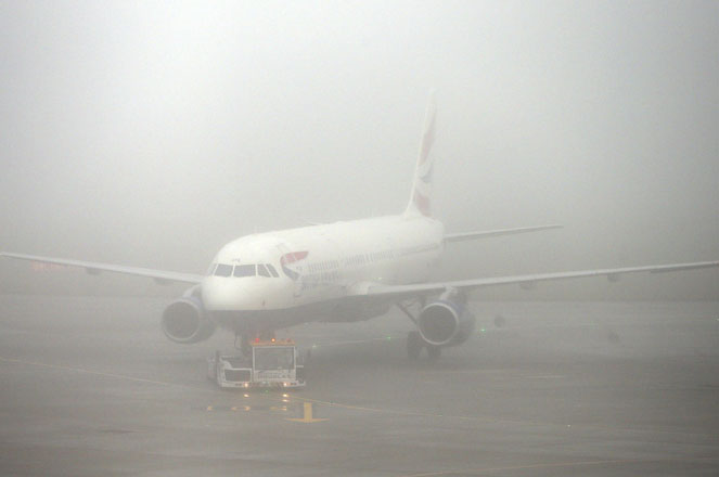A British Airways plane seen through fog at Terminal 5 Heathrow Airport, London, England, as thick fog disrupts flights at many UK airports for a second day, Monday Nov. 2, 2015. Around 45 flights have been canceled from Heathrow Airport as a yellow weather warning for fog covers much of England. (Steve Parsons / PA via AP) UNITED KINGDOM OUT - NO SALES - NO ARCHIVES