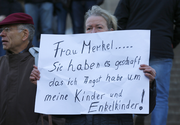 A woman holds up a placard reading 'Mrs Merkel you have achiedved that i'm afraid of the furture for my children and grandchildren' prior to a demonstration by anti-immigration right-wing movement PEGIDA (Patriotic Europeans Against the Islamisation of the West) in Cologne, Germany, January 9, 2016.  REUTERS/Wolfgang Rattay - RTX21MKQ