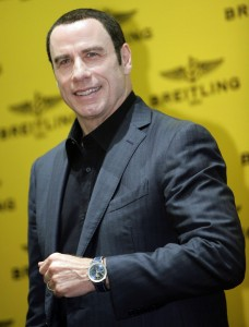 Actor John Travolta shows off his new watch before a news conference in Singapore