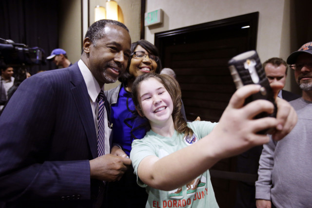 Republican presidential candidate Ben Carson, top left, and his wife Candy, top center, pose for a selfie with a young supporter after a town hall meeting Sunday, Feb. 21, 2016, in Reno, Nev. (AP Photo/Marcio Jose Sanchez)