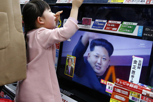 A girl watches a TV screen as all TV screens at an electronics store in Tokyo show a news program on North Korea's rocket launch with an image of North Korean leader Kim Jong Un, Sunday, Feb. 7, 2016. North Korea on Sunday defied international warnings and launched a long-range rocket that the United Nations and others call a cover for a banned test of technology for a missile that could strike the U.S. mainland. Japan's Prime Minister Shinzo Abe sharply criticized North Korea and said that the launch violated existing U.N. resolutions on Pyongyang's use of ballistic missile technology. (AP Photo/Shizuo Kambayashi)