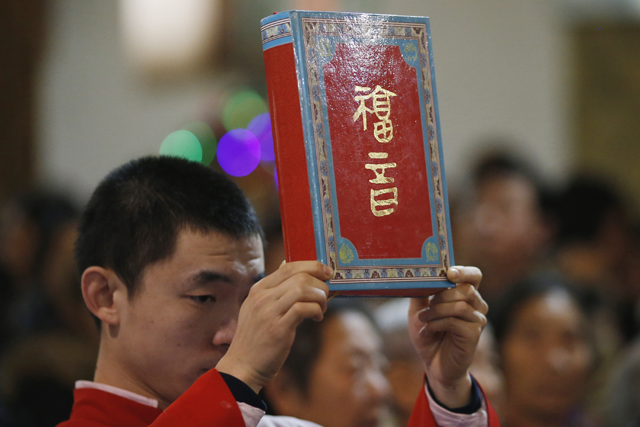"A page boy holds up a bible during a Christmas mass at a Catholic church in Beijing December 24, 2014. Christmas is not a traditional festival in China but is growing in popularity, especially in more metropolitan areas where young people go out to celebrate, give gifts and decorate their homes. The words on the cover read, ""gospel"". REUTERS/Kim Kyung-Hoon (CHINA - Tags: SOCIETY RELIGION) - RTR4J5ZL"