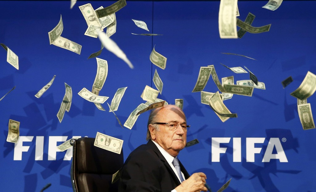 British comedian known as Lee Nelson (unseen) throws banknotes at FIFA President Sepp Blatter as he arrives for a news conference after the Extraordinary FIFA Executive Committee Meeting at the FIFA headquarters in Zurich, Switzerland July 20, 2015. World football's troubled governing body FIFA will vote for a new president, to replace Sepp Blatter, at a special congress to be held on February 26 in Zurich, the organisation said on Monday.       REUTERS/Arnd Wiegmann   TPX IMAGES OF THE DAY - RTX1L1TH