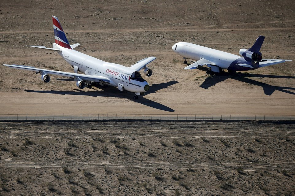 Old airplanes, including an Boeing 747-400, are stored in the desert in Victorville, California March 13, 2015. Last year, there were zero orders placed by commercial airlines for new Boeing 747s or Airbus A380s, reflecting a fundamental shift in the industry toward smaller, twin-engine planes. Smaller planes cost less to fly than the stately, four-engine jumbos, which can carry as many as 525 passengers. Picture taken March 13, 2015. To match Insight AEROSPACE-JUMBO    REUTERS/Lucy Nicholson