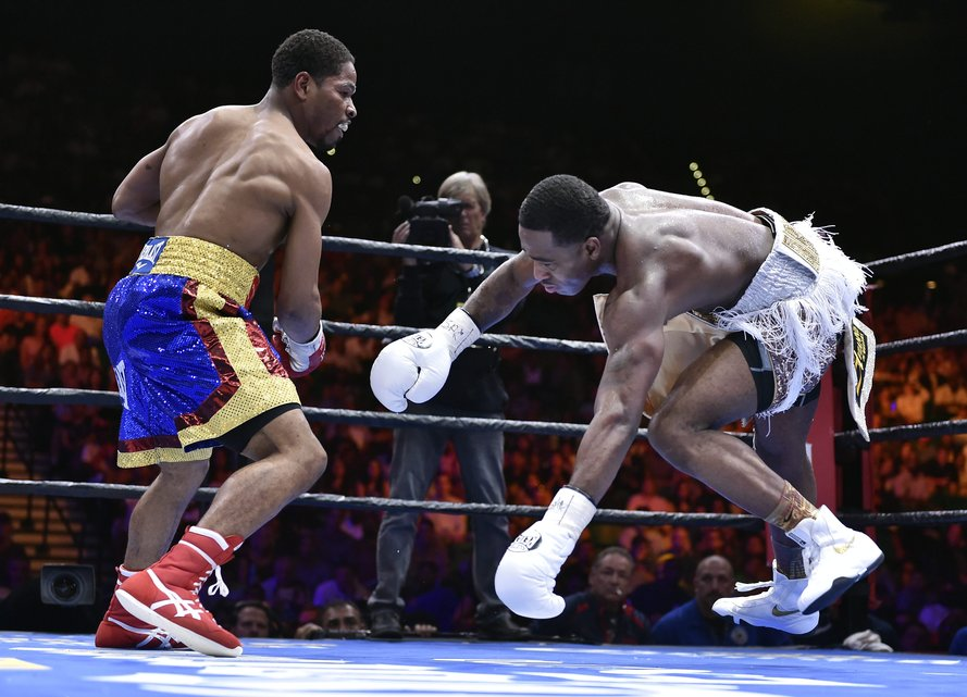 Shawn Porter, left, knocks Adrien Broner off-balance during a welterweight fight on Saturday, June 20, 2015, in Las Vegas. Porter won by unanimous decision after a 12-round bout. (AP Photo/David Becker)