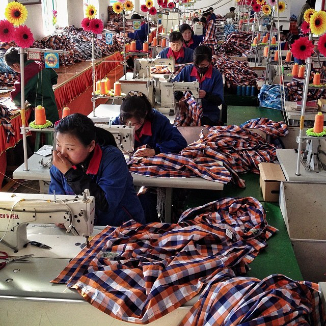 North Korean seamstresses work at rows of sewing machines at the Sonbong Textile Factory inside the Rason Special Economic Zone. (AP Photo/David Guttenfelder)