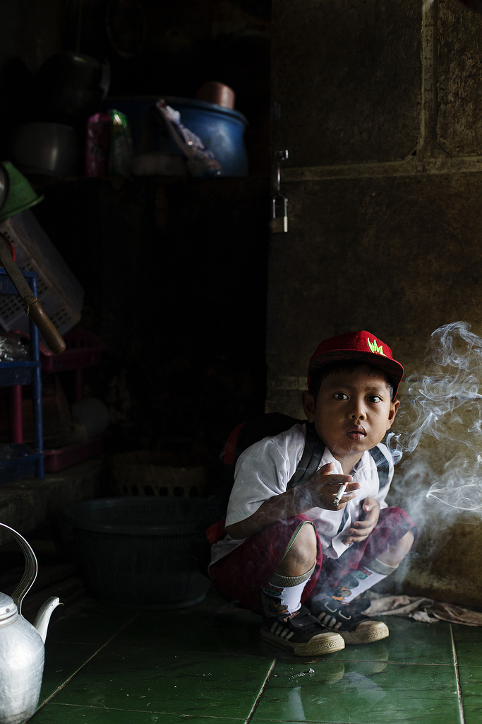 Dihan Muhamad, who has smoked up to two packs of cigarettes a day before cutting down, poses for a photo as he has his first cigarette at 7AM at his home before he attends his first grade class on February 10, 2014. (Photo By: Michelle Siu)