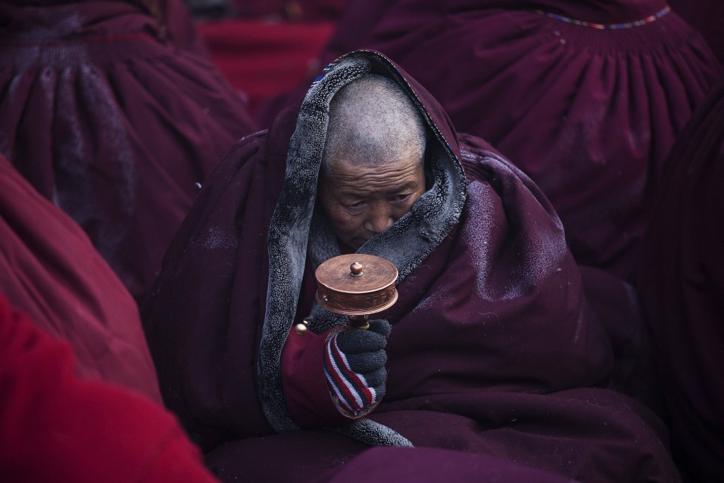 A Tibetan Buddhist nun spins a prayer wheel in sub zero temperatures at a Buddhist laymen lodge where thousands of people gather for daily chanting session during the Utmost Bliss Dharma Assembly, the last of the four Dharma assemblies at Larung Wuming Buddhist Institute in remote Sertar county, Garze Tibetan Autonomous Prefecture, Sichuan province, China November 1, 2015. The eight-day gathering of people chanting mantras and listening to teachings of monks starts every year around the 22nd of the ninth month on Tibetan calendar, the great day of Buddha's Descending from Tushita Heavens. The Larung Wuming Buddhist Institute, located some 3700 to 4000 metres above the sea level was founded in 1980 by Khenpo Jigme Phuntsok, an influential lama of Nyingma sect of Tibetan buddhism with only around 30 students but is now widely known as one of the biggest centres to study Tibetan Buddhism in the world. Picture taken November 1, 2015. REUTERS/Damir Sagolj