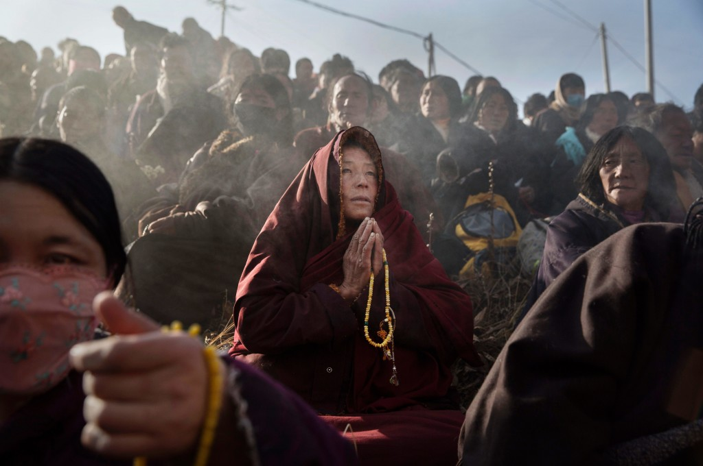 SERTAR, CHINA - OCTOBER 30: A Tibetan Buddhist monk prays with lay people on a hillside during a morning chanting session as part of the annual Bliss Dharma Assembly at the Larung Wuming Buddhist Institute on October 30, 2015 in Sertar county, in the remote Garze Tibetan Autonomous Prefecture, Sichuan province, China. The last of four annual assemblies, the week long annual gathering takes place in the ninth month of the Tibetan calendar and marks Buddha's descent from the heavens. Located high in the mountains of Sichuan, the Larung Wuming Buddhist Institute was founded in 1980 by an influential lama of the Nyingma sect and is widely regarded as the world's largest and most influential centres for Tibetan Buddhist studies. The school is home to thousands of monks and nuns and is popular for followers from all over the Tibetan areas and other parts of China. (Photo by Kevin Frayer/Getty Images)
