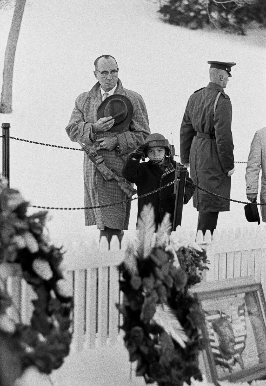 USA. Washington, D.C. 1963. A father and boy with a toy helmet and gun give a salute at the grave of John F. Kennedy in Arlington cemetary.
