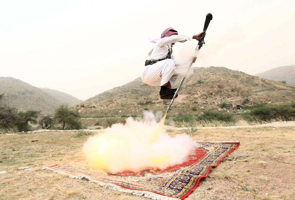A man fires a weapon as he dances during a traditional excursion near the western Saudi city of Taif, August 8, 2015. Saudis usually party in such excursions as they celebrate weddings or graduations. REUTERS/Mohamed Al Hwaity TPX IMAGES OF THE DAY FOR BEST QUALITY IMAGE ALSO SEE: GF10000171403 - RTX1NM14