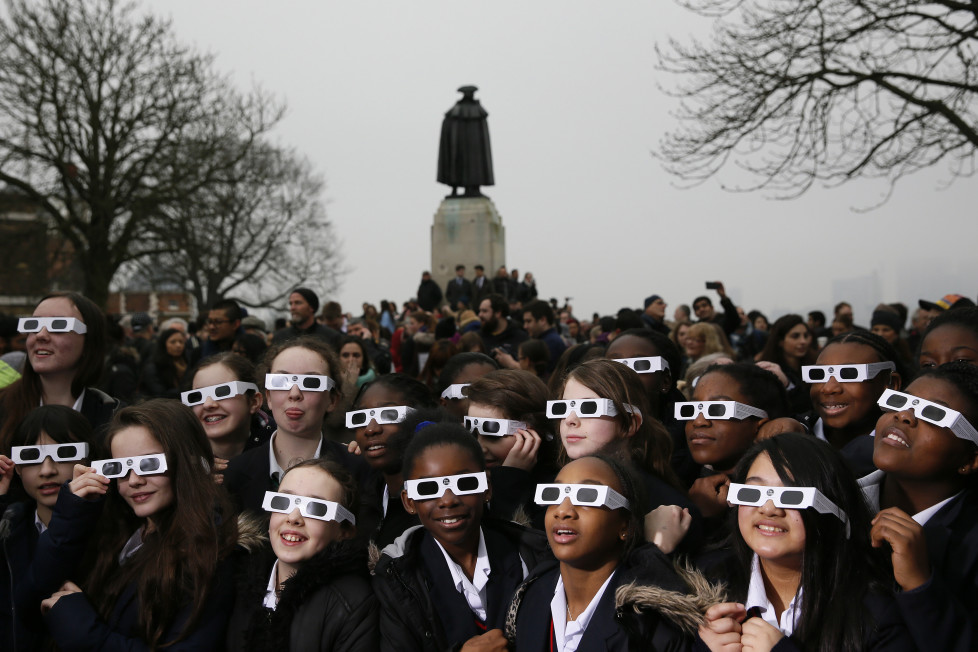 School children wearing protective glasses pose for photographers outside The Royal Observatory during a partial solar eclipse in Greenwich, south east London March 20, 2015. REUTERS/Stefan Wermuth - RTR4U555