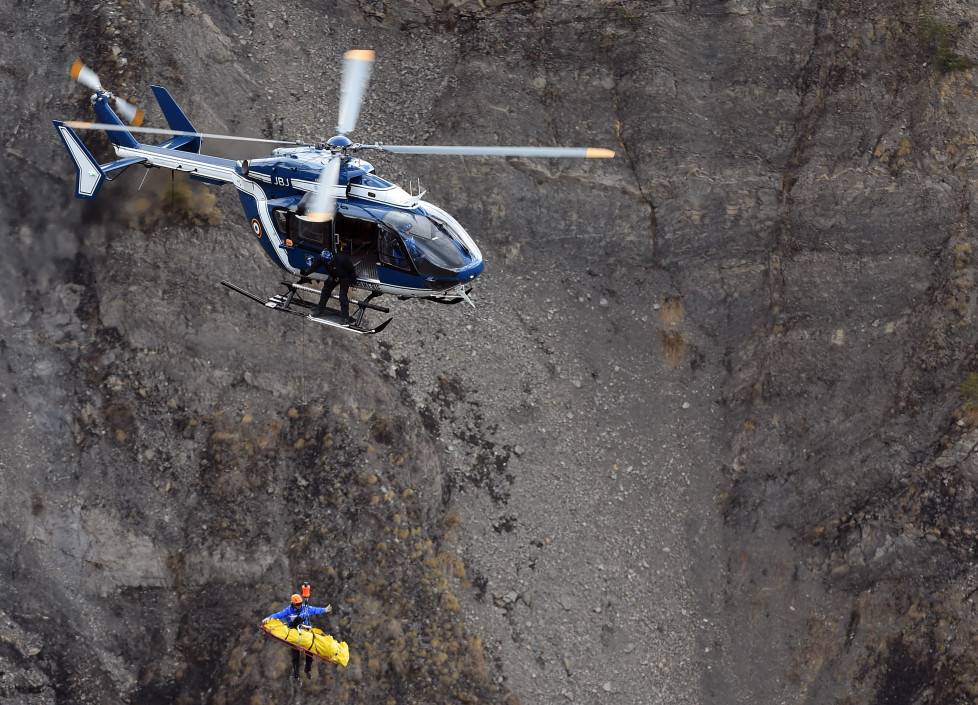 """A French gendarmerie's helicopter lifts an investigator on March 26, 2015 near scattered debris on the crash site of the Germanwings Airbus A320 that crashed in the French Alps above the southeastern town of Seyne. The young co-pilot of the doomed Germanwings flight that crashed on March 24, appears to have """"deliberately"""" crashed the plane into the French Alps after locking his captain out of the cockpit, but is not believed to be part of a terrorist plot, French officials said on March 26, 2015. AFP PHOTO / ANNE-CHRISTINE POUJOULAT / AFP / ANNE-CHRISTINE POUJOULAT"""