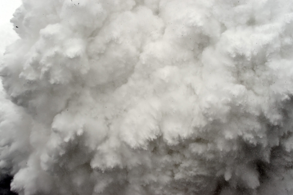 In this photograph taken on April 25, 2015, a cloud of snow and debris triggered by an earthquake flies towards Everest Base Camp, moments ahead of flattening part of the camp in the Himalayas. Rescuers in Nepal are searching frantically for survivors of a huge quake on April 25, that killed nearly 2,000, digging through rubble in the devastated capital Kathmandu and airlifting victims of an avalanche at Everest base camp. AFP PHOTO/ROBERTO SCHMIDT / AFP / ROBERTO SCHMIDT