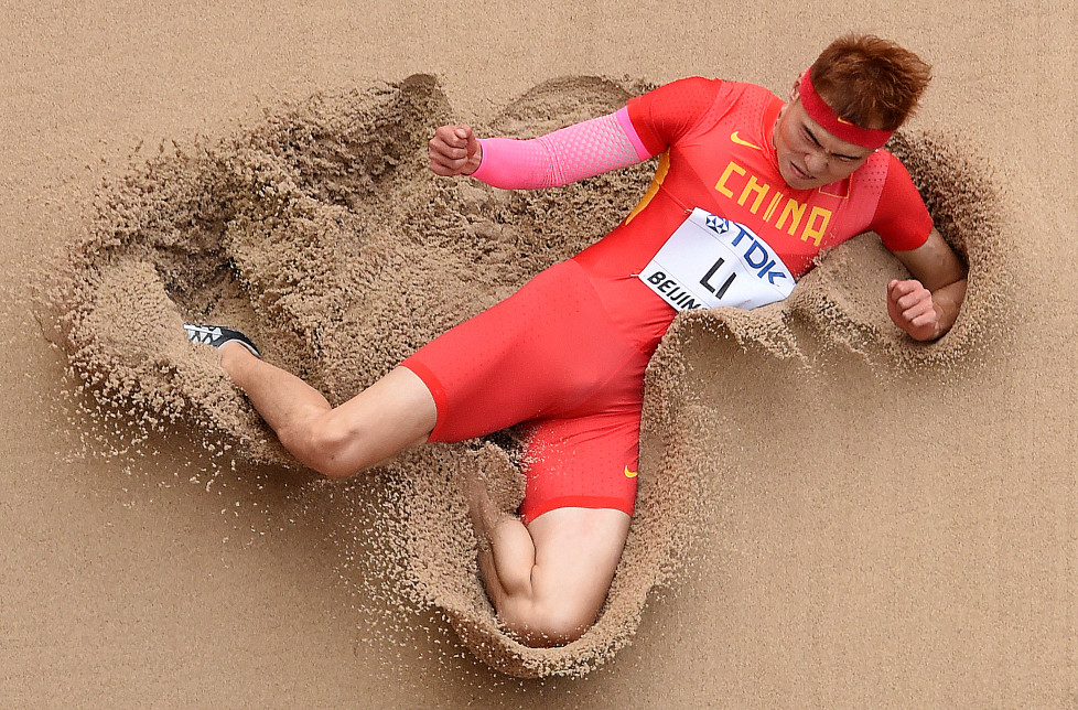"""China's Li Jinzhe competes in the qualifying round of the men's long jump athletics event at the 2015 IAAF World Championships at the """"Bird's Nest"""" National Stadium in Beijing on August 24, 2015. AFP PHOTO / ANTONIN THUILLIER / AFP / ANTONIN THUILLIER"""