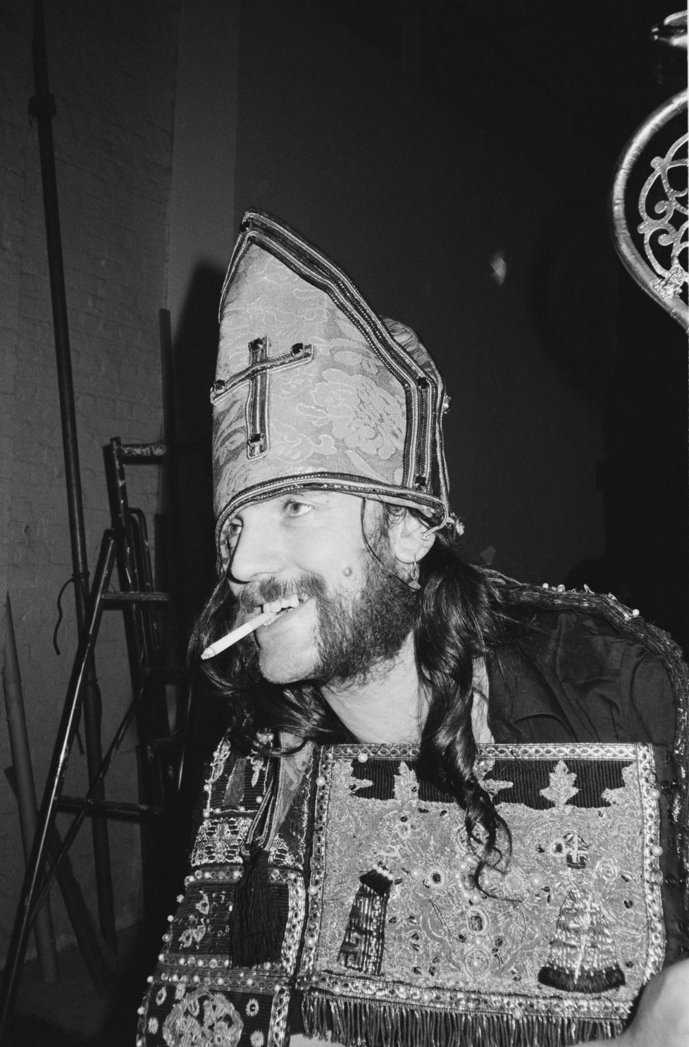 LONDON - 1st JULY: Lemmy Kilmister from Motorhead posed wearing a bishop's mitre hat and smoking a cigarette during the photo session for the 'Killed By Death' single in Pimlico, london in July 1984. (Photo by Fin Costello/Redferns)