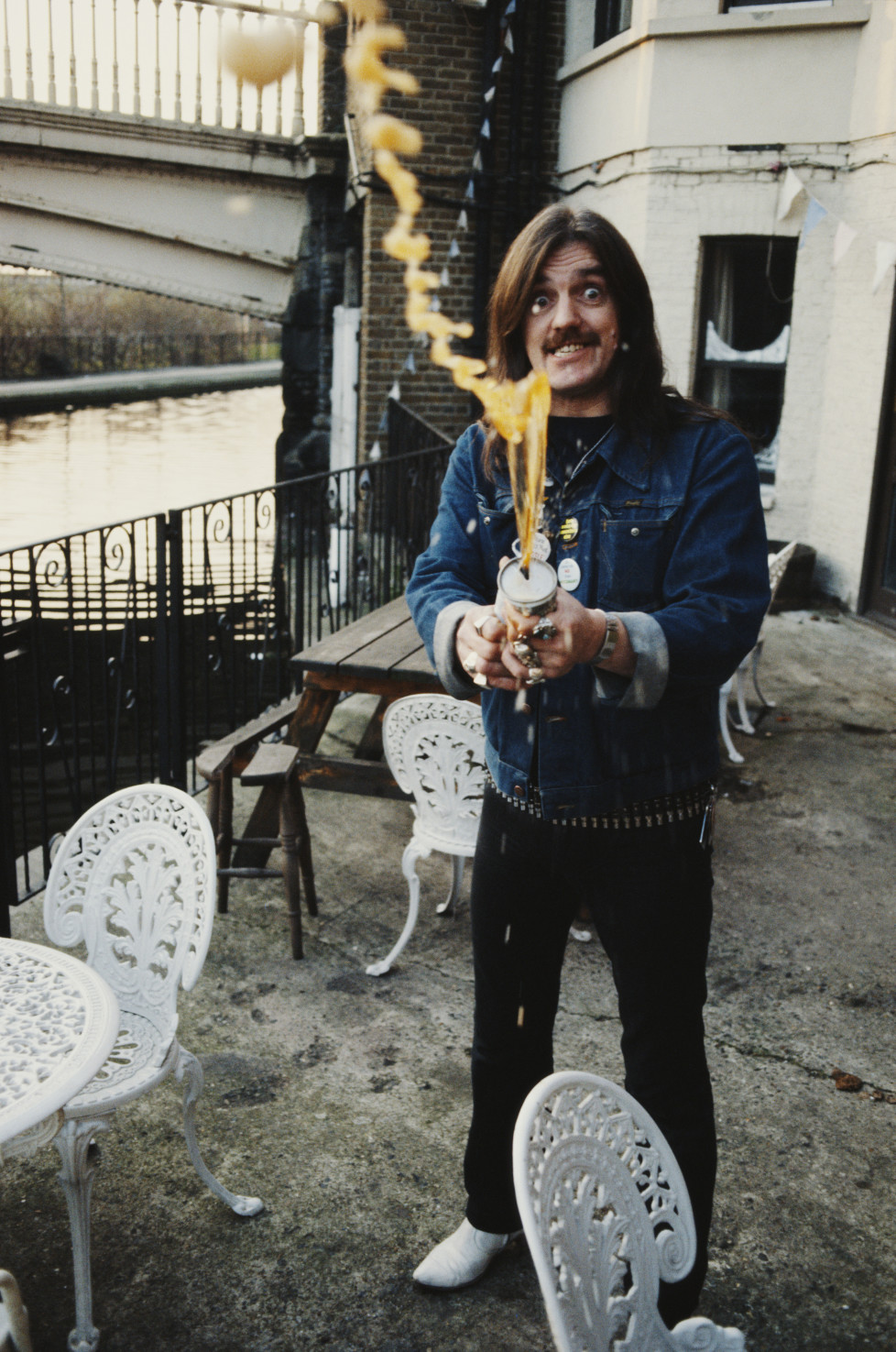 English rock musician and lead vocalist of the rock and roll band Motörhead, Lemmy (Ian Fraser 'Lemmy' Kilmister), spraying beer outside the Carlton Bridge Tavern, Grand Union Canal, London, circa 1985. (Photo by Tony Mottram/Getty Images)