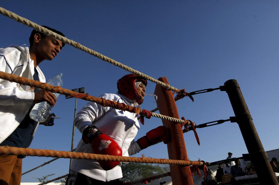 "Urooj, 15, spits water between rounds in her bout during the Sindh Junior Sports Association Boxing Tournament in Karachi, Pakistan February 21, 2016. For the past six months about a dozen girls, aged 8 to 17, have gone to the Pak Shine Boxing Club after school to practice their jabs, hooks and upper cuts. Pakistani women have been training as boxers in small numbers and competed in the South Asian Games last year, said Younis Qambrani, the coach who founded the club in 1992 in the Karachi neighbourhood of Lyari, better known for internecine gang warfare than for breaking glass ceilings. REUTERS/Akhtar Soomro SEARCH ""THE WIDER IMAGE"" FOR ALL STORIES TPX IMAGES OF THE DAY"