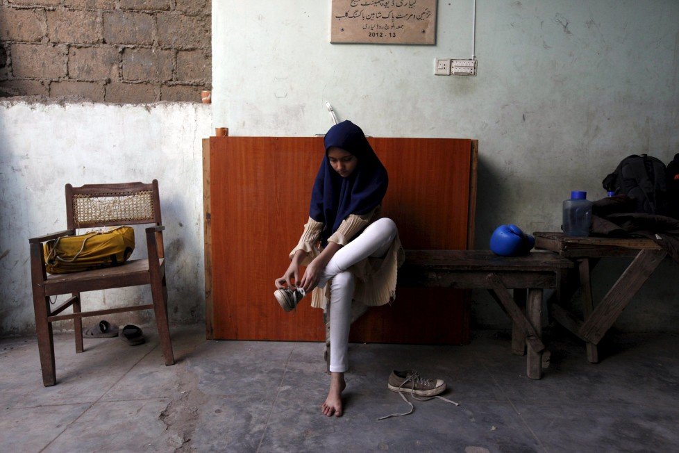 "REFILE - CLARIFYING NAME OF BOXING CLUBTabia, 12, removes her shoes after finishing an exercise session at the first women's boxing coaching camp in Karachi, Pakistan February 19, 2016. For the past six months about a dozen girls, aged 8 to 17, have gone to the Pak Shaheen Boxing Club after school to practice their jabs, hooks and upper cuts. Pakistani women have been training as boxers in small numbers and competed in the South Asian Games last year, said Younis Qambrani, the coach who founded the club in 1992 in the Karachi neighbourhood of Lyari, better known for internecine gang warfare than for breaking glass ceilings. REUTERS/Akhtar Soomro SEARCH ""THE WIDER IMAGE"" FOR ALL STORIES"