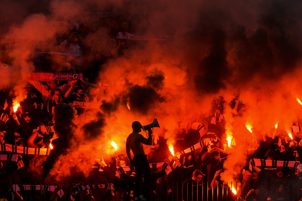 Supporters of Bosnia-Herzegovina celebrates after their team scores the second goal during the friendly football match between Switzerland and Bosnia-Herzegovina at Letzigrund Stadium in Zurich on March 29, 2016. / AFP / FABRICE COFFRINI