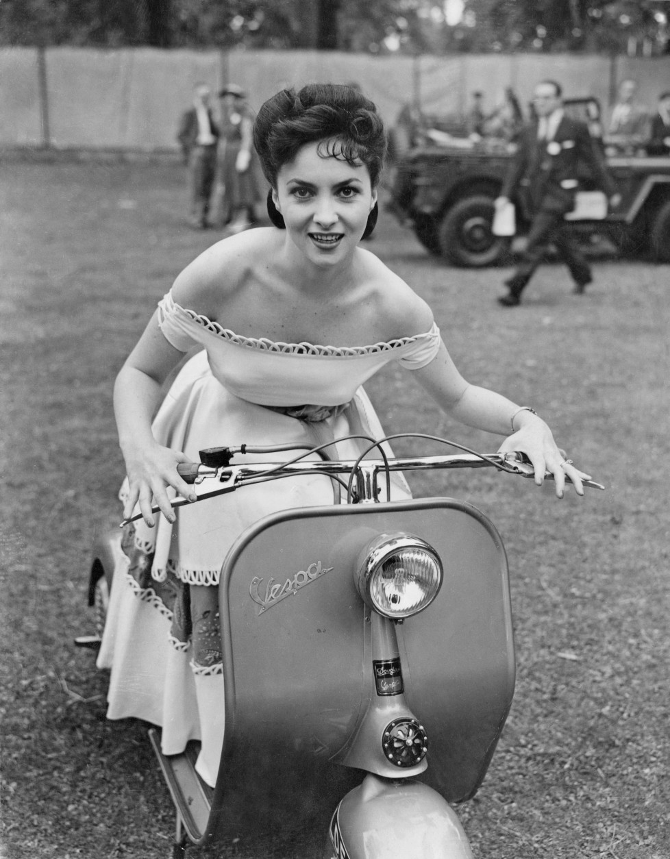 14th June 1952: Italian actress Gina Lollobrigida attends the Great Film Garden Party at Morden Hall Park in Surrey, on a Vespa motor scooter. She is in Britain to promote an Italian Film Festival. (Photo by Ron Case/Keystone/Getty Images)