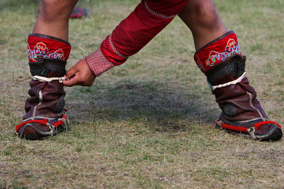 A Mongolian wrestler strings his boot at a camp in the grasslands town of Suuj, about 60 km (37 miles) north of the capital Ulan Bator, July 5, 2006. Mongolians celebrate their annual festival of Naadam, a pageant of wrestling, hoseback-riding and archery, on July 11. This year's will be bigger than ever as Mongolians mark the 800 years since Genghis Khan united the nation. REUTERS/Nir Elias (MONGOLIA) - RTR1F7RC