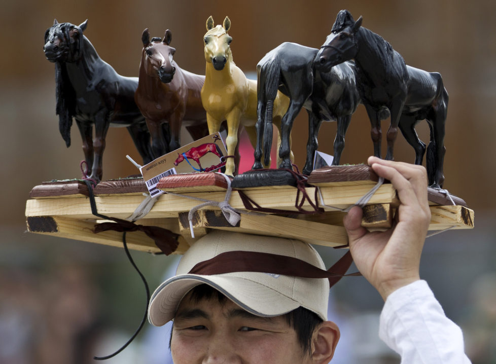 A Mongolian vendor displays figure horses for sale during the Naadam Festival in Ulan Bator, Mongolia, Wednesday, July 11, 2012. Mongolians celebrate the anniversary of Genghis Khan's march to world conquest on July 11 with the annual sports festival featuring traditional Mongolian events including wrestling, archery, and horse racing. (AP Photo/Andy Wong)