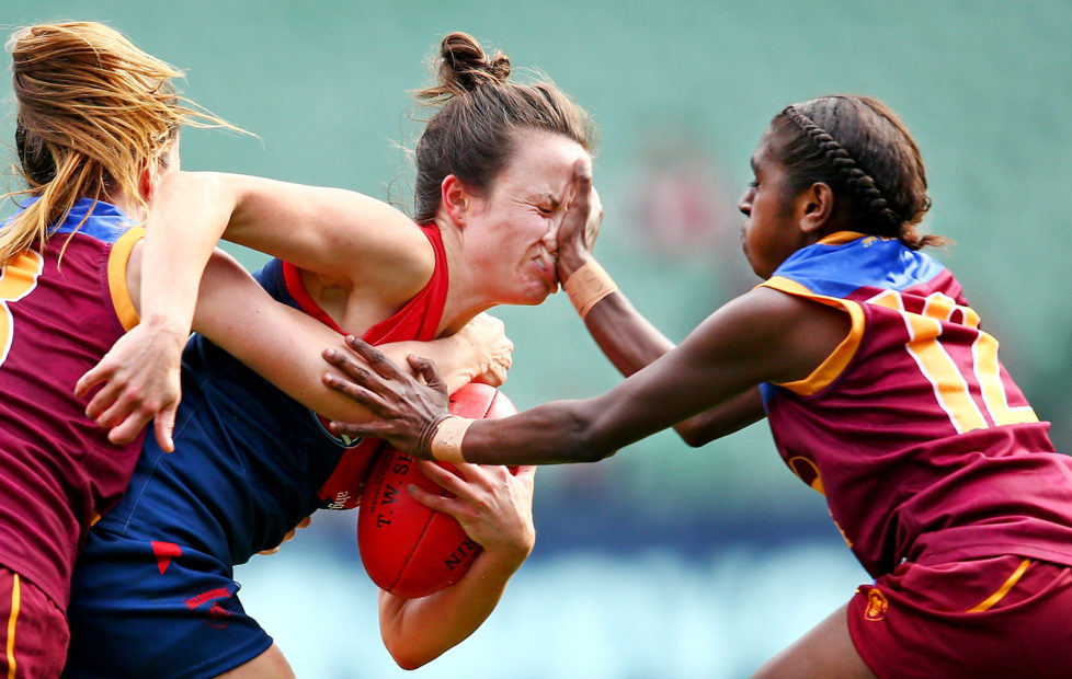 MELBOURNE, VICTORIA - MAY 22: Daisy Pearce of Melbourne is tackled by Emily Bates of Brisbane and Delma Gisu of Brisbane during the 2016 AFL Womens match between the Melbourne Demons and the Brisbane Lions at the Melbourne Cricket Ground on May 22, 2016 in Melbourne, Australia. (Photo by Scott Barbour/AFL Media/Getty Images)