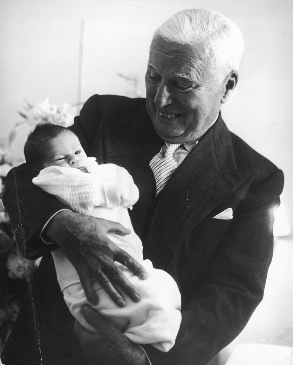 Comic actor Charlie Chaplin (1889 - 1977) holding his week-old son Christopher at the Mont-Choisi Clinic, Lausanne, Switzerland, 14th July 1962. Christopher is his eighth and last child with Oona O'Neill. (Photo by Daily Express/Archive Photos/Getty Images)
