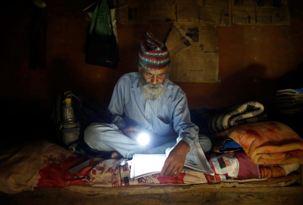 "Durga Kami, 68, who is studying in the tenth grade at Shree Kala Bhairab Higher Secondary School, uses a torch to read a book during a power cut, at his one-room house in Syangja, Nepal, June 4, 2016. REUTERS/Navesh Chitrakar. SEARCH ""DURGA KAMI"" FOR THIS STORY. SEARCH ""THE WIDER IMAGE"" FOR ALL STORIES"