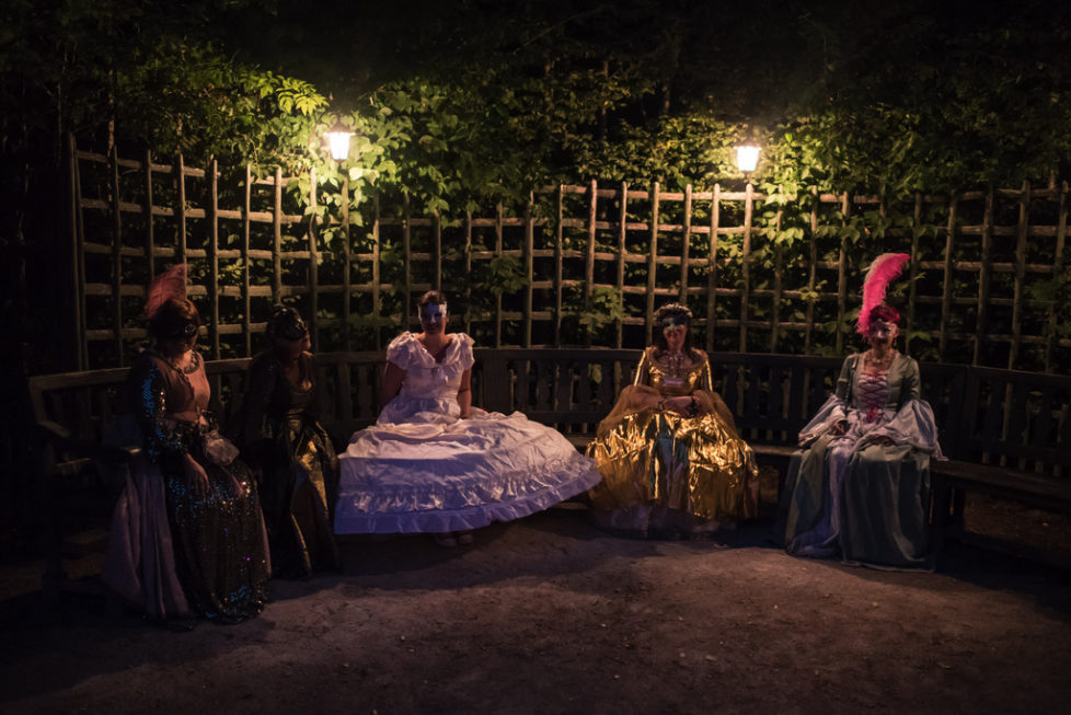 Costumed guests sit in the gardens of the Versailles castle before the Great Masked Bal, in Versailles, west of Paris, Saturday, June 27, 2015. On the occasion of the tercentenary of King Louis XIV's death, who died on Sept.1, 1715, a fountains show and a costumed ball took place in the castle.(AP Photo/Kamil Zihnioglu)