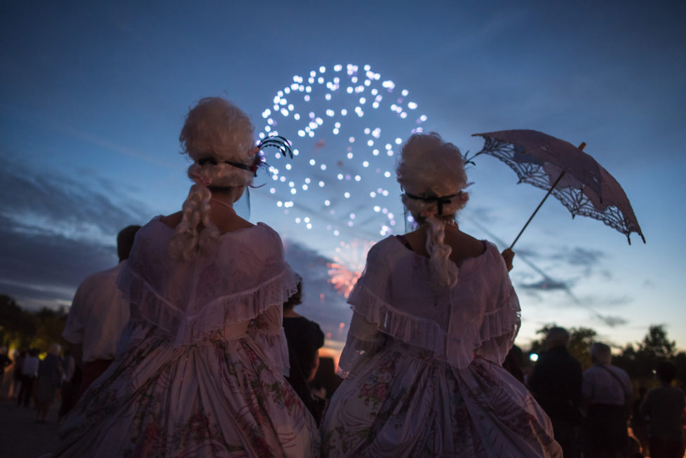 Costumed guests watch fireworks in the gardens of the Versailles castle before the Great Masked Bal, in Versailles, west of Paris, Saturday, June 27, 2015. On the occasion of the tercentenary of King Louis XIV's death, who died on Sept.1, 1715, a fountains show and a costumed ball took place in the castle.(AP Photo/Kamil Zihnioglu)