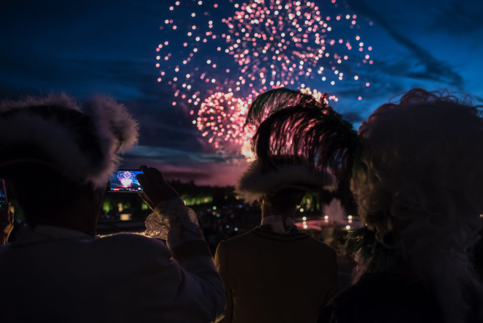 Costumed guests watch fireworks before the Great Masked Bal, in the Versailles castle, west of Paris, Saturday, June 27, 2015. On the occasion of the tercentenary of King Louis XIV's death, who died on Sept.1, 1715, a fountains show and a costumed ball took place in the castle.(AP Photo/Kamil Zihnioglu)