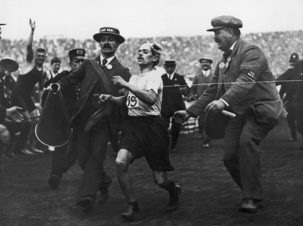 Dorando Pietri of Italy, on the verge of collapse, is helped across the finish line in the Marathon event of the Olympic Games in London, 24th July 1908. He was subsequently disqualified and the title was given to John Hayes of the USA. (Photo by Hulton Archive/Getty Images)